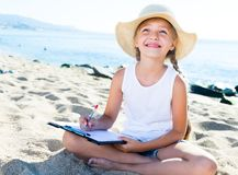 Child girl in hat writes draws dreams with sand on seashore. In summer Stock Photography