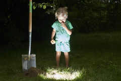 Child girl have unearthed a treasure in the grass Royalty Free Stock Images
