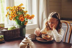 Child girl having breakfast at home in autumn morning. Real life cozy modern interior in country house Royalty Free Stock Images
