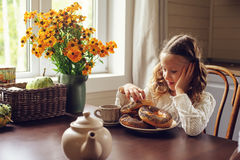 Child girl having breakfast at home in autumn morning. Real life cozy modern interior in country house Stock Images