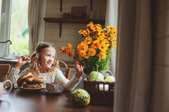 Child girl having breakfast at home in autumn morning. Real life cozy modern interior in country house Stock Photos