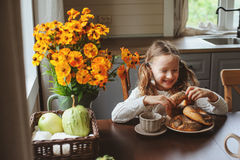 Child girl having breakfast at home in autumn morning. Real life cozy modern interior in country house Stock Photography