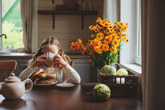 Child girl having breakfast at home in autumn morning. Real life cozy modern interior in country house. Kid eating bagels and drinking tea Royalty Free Stock Image