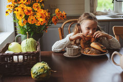 Child girl having breakfast at home in autumn morning. Real life cozy modern interior in country house Royalty Free Stock Photography