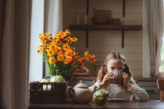 Child girl having breakfast at home in autumn morning. Real life cozy modern interior in country house. Kid eating bagels and drinking tea stock photo