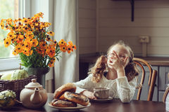 Child girl having breakfast at home in autumn morning. Real life cozy modern interior in country house. Kid eating bagels and drinking tea Royalty Free Stock Photography