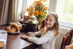 Child girl having breakfast at home in autumn morning. Real life cozy modern interior in country house Stock Image