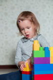 Child girl having fun and build of bright plastic construction blocks stock images