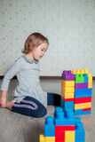 Child girl having fun and build of bright plastic construction blocks royalty free stock images