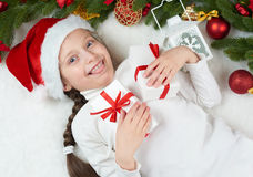 Child girl having fun with christmas decoration, face expression and happy emotions, dressed in santa hat, lie on white fur backgr Stock Image