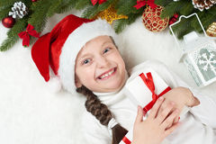 Child girl having fun with christmas decoration, face expression and happy emotions, dressed in santa hat, lie on white fur backgr Royalty Free Stock Images