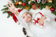 Child girl having fun with christmas decoration, face expression and happy emotions, dressed in santa hat, lie on white fur backgr Stock Images