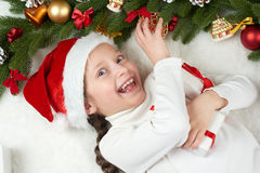 Child girl having fun with christmas decoration, face expression and happy emotions, dressed in santa hat, lie on white fur backgr. Ound, winter holiday concept royalty free stock photography