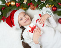 Child girl having fun with christmas decoration, face expression and happy emotions, dressed in santa hat, lie on white fur backgr. Ound, winter holiday concept royalty free stock photo