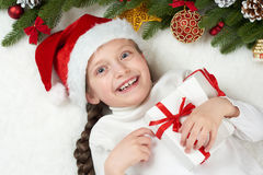 Child girl having fun with christmas decoration, face expression and happy emotions, dressed in santa hat, lie on white fur backgr. Ound, winter holiday concept royalty free stock images