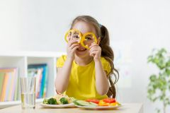 Child girl having fun with food vegetables at kitchen. Kid girl having fun with food vegetables at kitchen Stock Images
