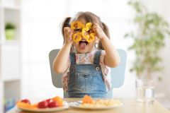 Child girl having fun with food vegetables at nursery room. Kid girl having fun with food vegetables at nursery room royalty free stock photo