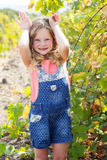 Child girl having fun in garden of grapes Stock Photo