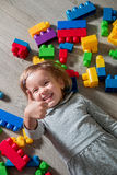 Child girl having fun and lying on the floor near bright plastic construction blocks. Toddler playing. Developing toys. Early lear Stock Image