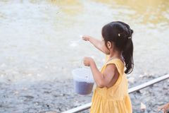 Child girl having fun to feed and give food to fish Royalty Free Stock Image