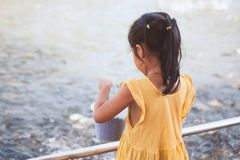 Child girl having fun to feed and give food to fish Stock Images