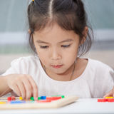 child girl having fun to play and learn magnetic alphabets Stock Image