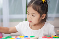 Child girl having fun to play and learn magnetic alphabets Royalty Free Stock Photos