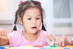 Child girl having fun to play and learn magnetic alphabets Royalty Free Stock Image