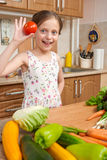 Child girl having fun with tomatoes, fruits and vegetables in home kitchen interior, healthy food concept Royalty Free Stock Image