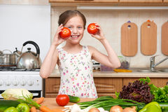 Child girl having fun with tomatoes. Home kitchen interior with Royalty Free Stock Photo