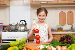Child girl having fun with tomatoes. Home kitchen interior with Stock Image