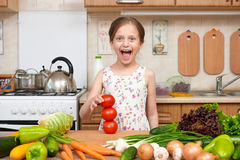 Child girl having fun with tomatoes. Home kitchen interior with fruits and vegetables. Healthy food concept Stock Image