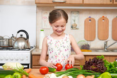 Child girl having fun with tomatoes. Home kitchen interior with fruits and vegetables. Healthy food concept Stock Images