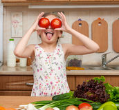 Child girl having fun with tomatoes, look through like binoculars, fruits and vegetables in home kitchen interior, healthy food co Royalty Free Stock Photography
