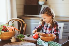 Child girl helps mom to cook and cut fresh vegetables for salad with knife Royalty Free Stock Photo
