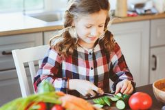 Child girl helps mom to cook and cut fresh vegetables for salad with knife Royalty Free Stock Photos