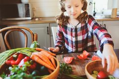 Child girl helps mom to cook and cut fresh vegetables for salad with knife Stock Photos