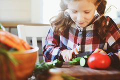 Child girl helps mom to cook and cut fresh vegetables for salad with knife Stock Photography