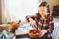 Child girl helps mom to cook and cut fresh vegetables for salad with knife Stock Photo