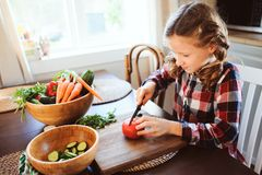 Child girl helps mom to cook and cut fresh vegetables for salad with knife Royalty Free Stock Images