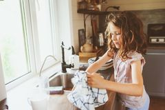 Child girl helps mother at home and wash dishes in kitchen. Casual lifestyle in real interior Royalty Free Stock Photography