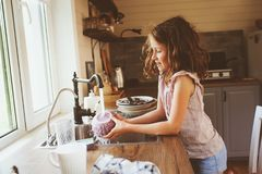 Child girl helps mother at home and wash dishes in kitchen. Casual lifestyle in real interior Stock Photos