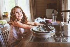 Child girl helps mother at home and wash dishes in kitchen. Casual lifestyle in real interior Stock Image
