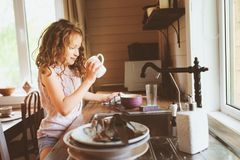 Child girl helps mother at home and wash dishes in kitchen. Casual lifestyle in real interior Royalty Free Stock Photos