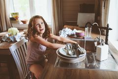 Child girl helps mother at home and wash dishes in kitchen. Casual lifestyle in real interior Royalty Free Stock Images