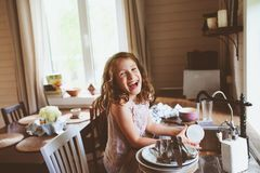 Child girl helps mother at home and wash dishes in kitchen. Casual lifestyle in real interior Royalty Free Stock Photo