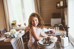 Child girl helps mother at home and wash dishes in kitchen. Casual lifestyle in real interior Stock Photography