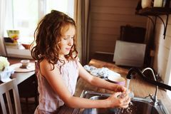 Child girl helps mother at home and wash dishes in kitchen. Casual lifestyle in real interior. Teaching kids to do house work Stock Photos