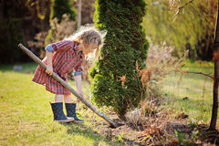 Child girl helps in spring garden with shovel Royalty Free Stock Images