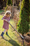 Child girl helps in spring garden with shovel Stock Photo